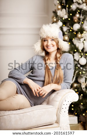 Beautiful young woman  at the Christmas tree. Beautiful girl celebrates Christmas - stock photo