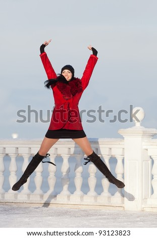 Beautiful young woman at winter. Attractive brunette in red jumping in the winter park - stock photo