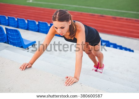 Beautiful young woman athlete runner performing push-up during warming up before training on a stadium stairs with seats and running track on background. Looking aside on the highest amplitude - stock photo