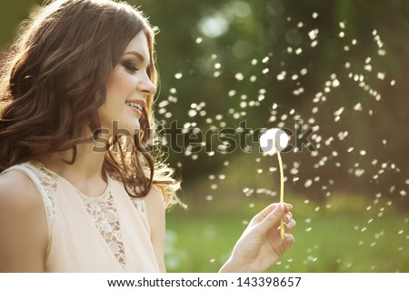 Beautiful young woman blowing a dandelion  - stock photo