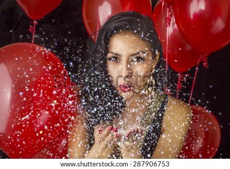 Beautiful young woman blowing confetti - stock photo