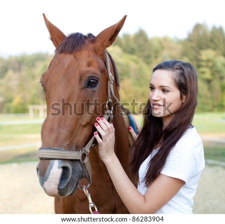 Beautiful young woman brushing a gorgeous horse - stock photo