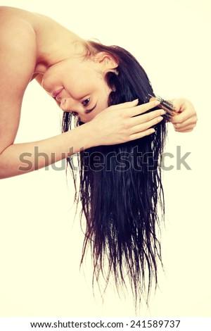 Beautiful young woman brushing hairs. - stock photo