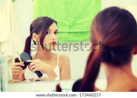 Beautiful young woman brushing her hair at bathroom - stock photo