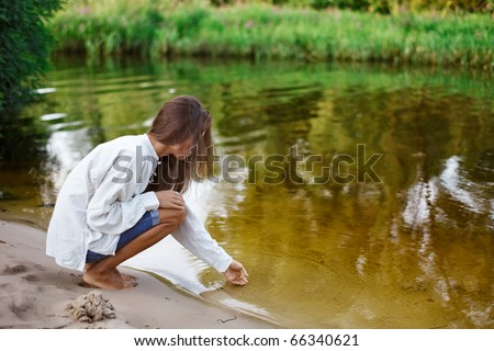 Beautiful young woman building sand castle on the lake coast - stock photo
