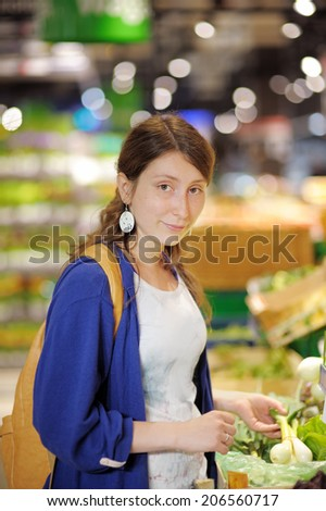 Beautiful young woman buying vegetables at supermarket  - stock photo