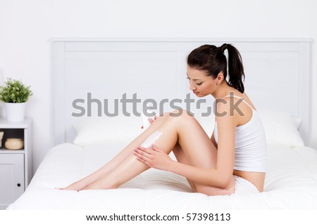 Beautiful young woman caring about her legs with moisturizing lotion - indoors - stock photo