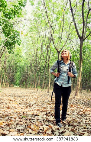 Beautiful young woman carrying backpack walking in forest looking on top the tree and smiley - stock photo