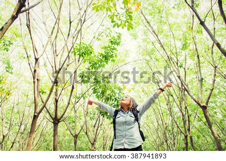 Beautiful young woman carrying backpack walking in forest stretch her hands happy with fresh air - stock photo