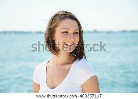 Beautiful young woman (Caucasian, in her 20-s, dark blonde, short hair (bob), natural makeup) with a happy smile, wearing a white v-neck t-shirt, looking to the side  - stock photo