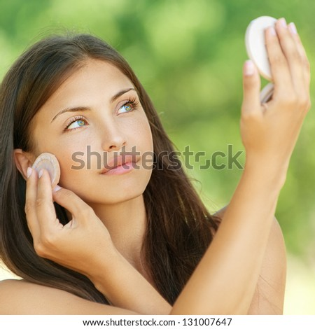 Beautiful young woman causes powder to skin, against summer green park. - stock photo