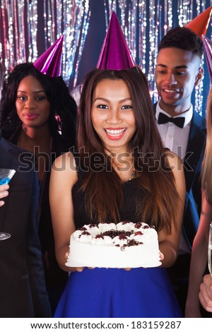 Beautiful young woman celebrating birthday with friends at nightclub - stock photo