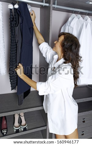 Beautiful young woman choosing an outfit from her wardrobe. - stock photo