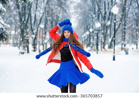 Beautiful young woman circling and enjoying the falling snow dressed in a cheerful blue winter scarf , hat and skirt. Dancing girl. - stock photo
