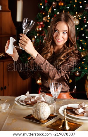 Beautiful young woman cleaning a glass at a well laid Christmas  - stock photo