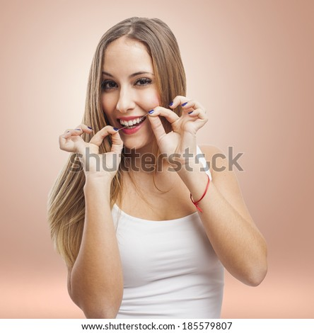 beautiful young woman cleaning her teeth with dental floss - stock photo