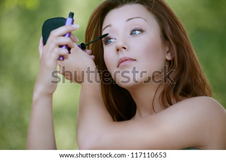 Beautiful young woman close-up colors lashes mascara, against background of summer green park. - stock photo