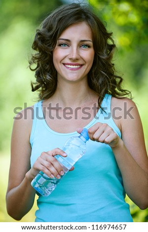 Beautiful young woman close-up in blue shirt holding bottle of water, against green of summer park. - stock photo