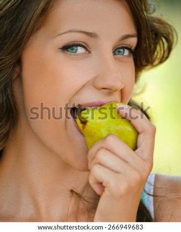 Beautiful young woman close-up in blue shirt pear bites, against green of summer park. - stock photo
