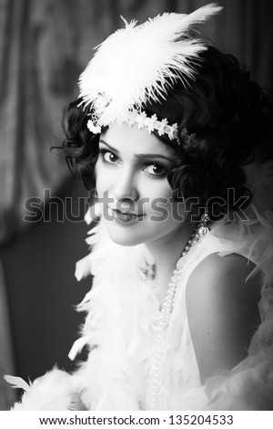 Beautiful young woman close up portrait in retro flapper style headband bw Vogue style vintage - stock photo