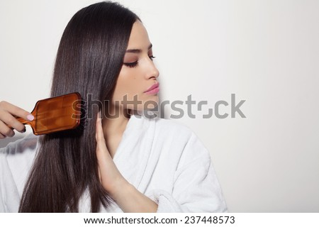 beautiful young woman combing her healthy and shiny hair, studio white - stock photo