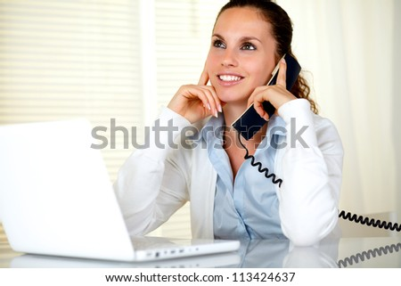 Beautiful young woman conversing on phone at workplace in front of laptop - stock photo
