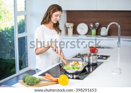 Beautiful young woman cooking food at home - stock photo