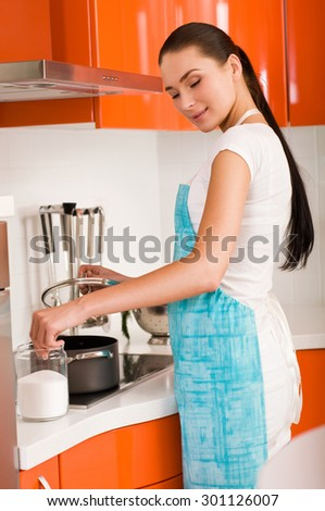 Beautiful young woman cooking in the kitchen, tasting soup - stock photo