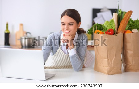 Beautiful young woman cooking looking at laptop screen with receipt in the kitchen - stock photo