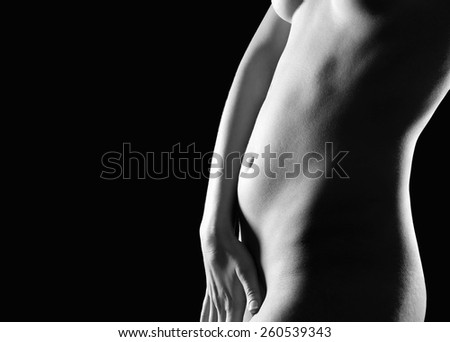 Beautiful young woman covering herself with her hand in front of black studio background, beauty concept, her private parts are not visible, monochrome photo - stock photo