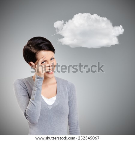 Beautiful young woman covers her eyes with hand, grey background - stock photo