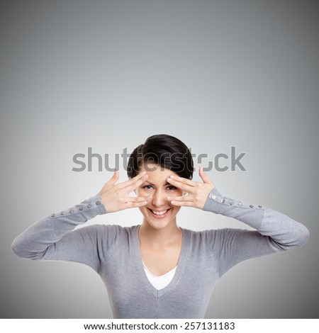 Beautiful young woman covers her eyes with hands, isolated on grey - stock photo