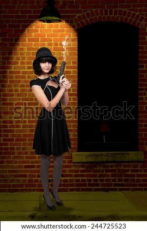 Beautiful young woman criminal with a gun - stock photo