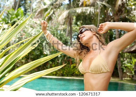 Beautiful young woman dancing in a golden bikini near a swimming pool in a topical garden during a sunny day on vacations. - stock photo