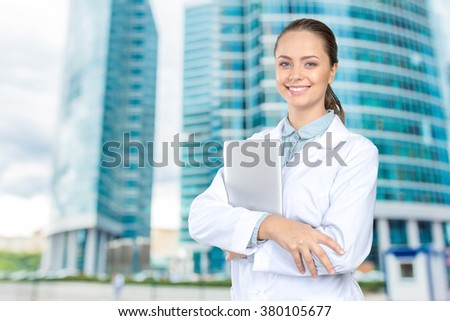 Beautiful young woman doctor holding laptop - stock photo