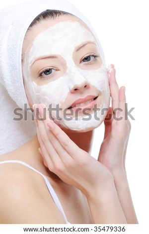 beautiful young woman doing cosmetic mask on her face - white background - stock photo