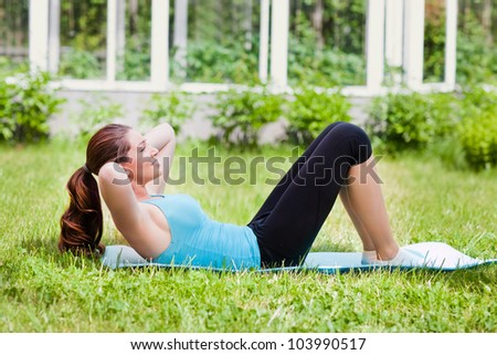 Beautiful young woman doing  exercises on green grass at park. - stock photo