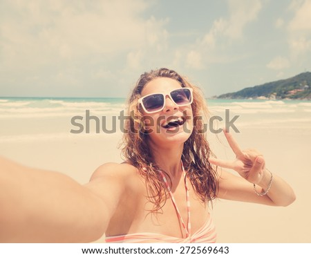 Beautiful young woman doing selfie on the beach - stock photo