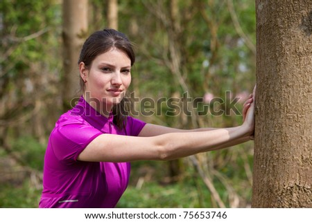 Beautiful young woman doing stretch exercises outdoors - stock photo