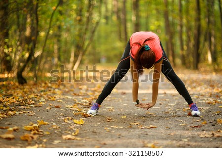 Beautiful young woman doing stretching exercise on road at park - stock photo