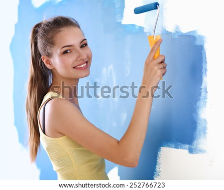 Beautiful young woman doing wall painting, standing on ladder - stock photo
