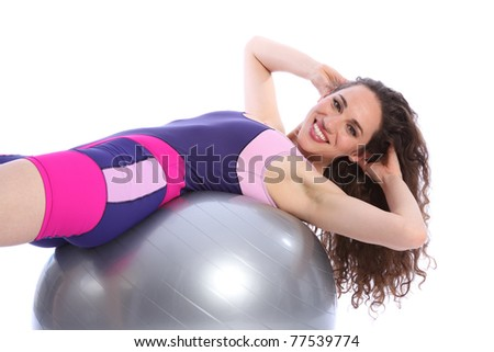 Beautiful young woman doing warm up fitness ball exercise routine. Woman has a happy smile and is wearing bright blue and pink sports clothes. - stock photo