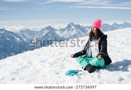Beautiful young woman doing yoga in the snow mountains. Winter Scenic in the French Alps, Les 2 Alpes - stock photo