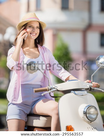 Beautiful young woman dressed casual sitting on scooter and talking on phone. - stock photo
