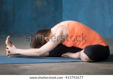 Beautiful young woman dressed in bright sportswear enjoying yoga indoors. Yogi girl working out in grunge interior with blue wall. Janu sirshasana or Head-to-Knee Forward Bend Pose - stock photo