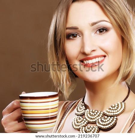 Beautiful young woman drinking coffee - stock photo