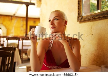 Beautiful young woman drinking coffee in a restaurant - stock photo
