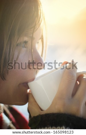Beautiful young woman drinking hot drink outside on a sunny cold winter morning - stock photo