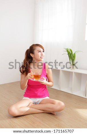Beautiful Young Woman drinking hot tea at home with wood floor in the morning, healthy lifestyle concept, asian beauty - stock photo