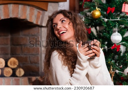 Beautiful young woman drinking tea at the Christmas tree. Beautiful girl celebrates Christmas with a cup of cocoa  in front of tree over living room - stock photo